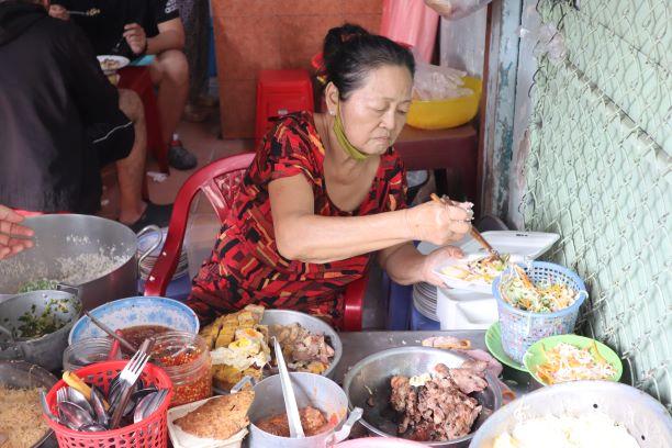 Diep Thi Ngoc Anh serves a dish of com tam to customer at Com Tam Chi Nam, Tan Canh Street, Tan Binh District, Ho Chi Minh City. Photo: Nam Vuong / Tuoi Tre