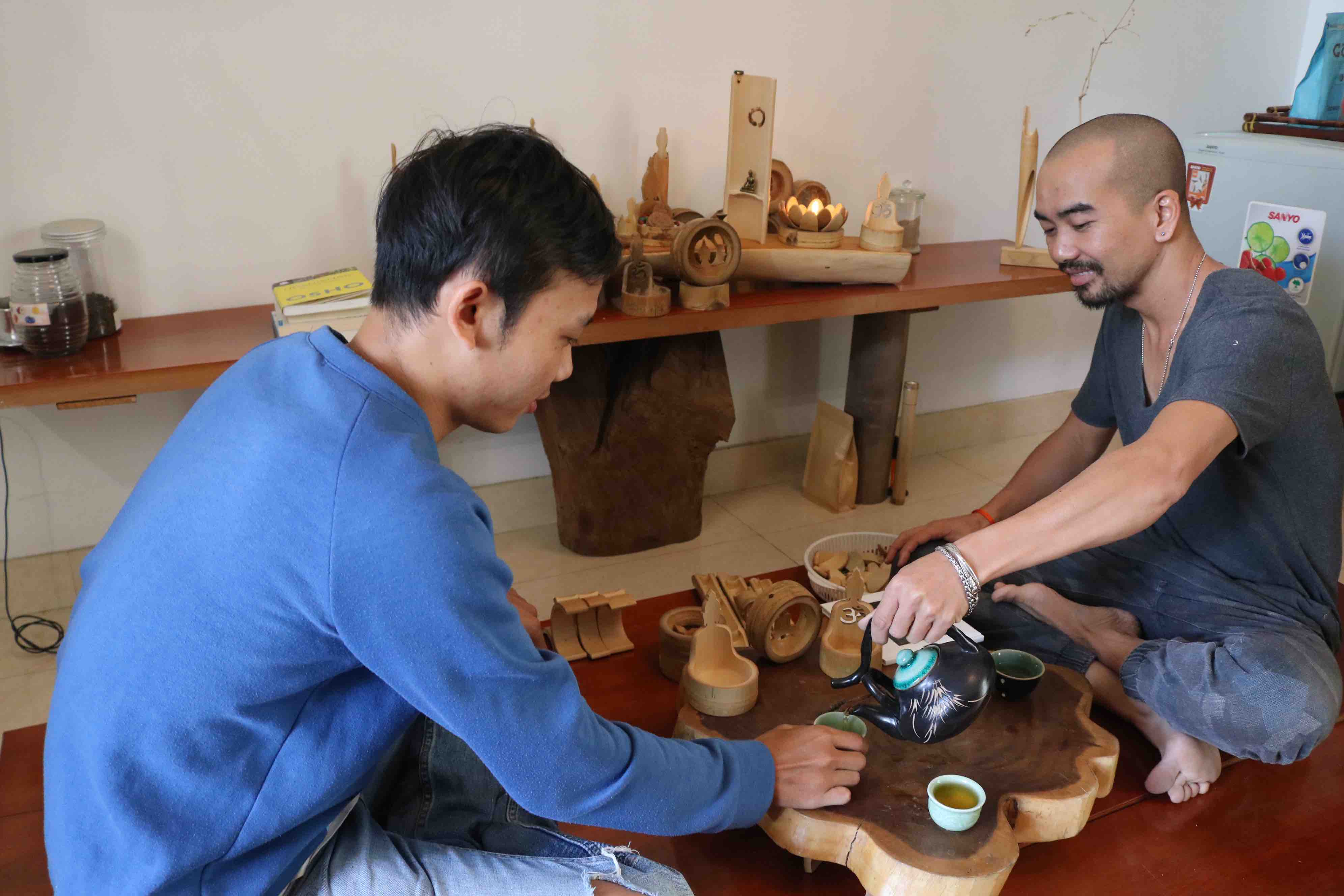 Customer Nguyen Huy Hung (left) visits the workshop to purchase decorative products and drink the tea with artist Nguyen Manh Cuong (right). Photo: Hoang An / Tuoi Tre