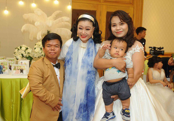 Nguyen Duy Phat and his wife, along with their baby son, are among the 40 physically challenging grooms and brides at a mass wedding organized in 2018 by Meritorious Artist Kim Cuong (center) in this supplied photo.