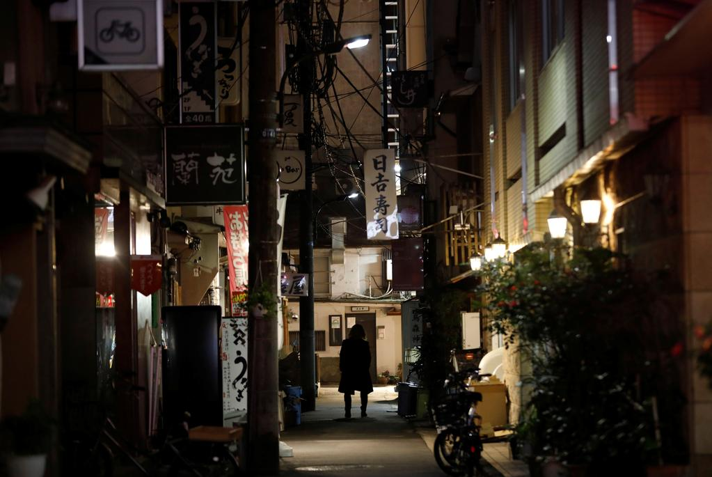A man walks past restaurants which closed after 8 PM, the time the government asks them to close by, amid the coronavirus emergency decree in Tokyo, Japan, January 15, 2021. Photo: Reuters