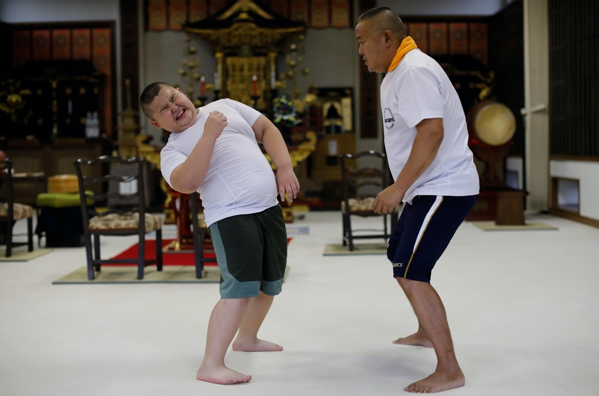 Kyuta practices sumo with his father. Photo: Reuters