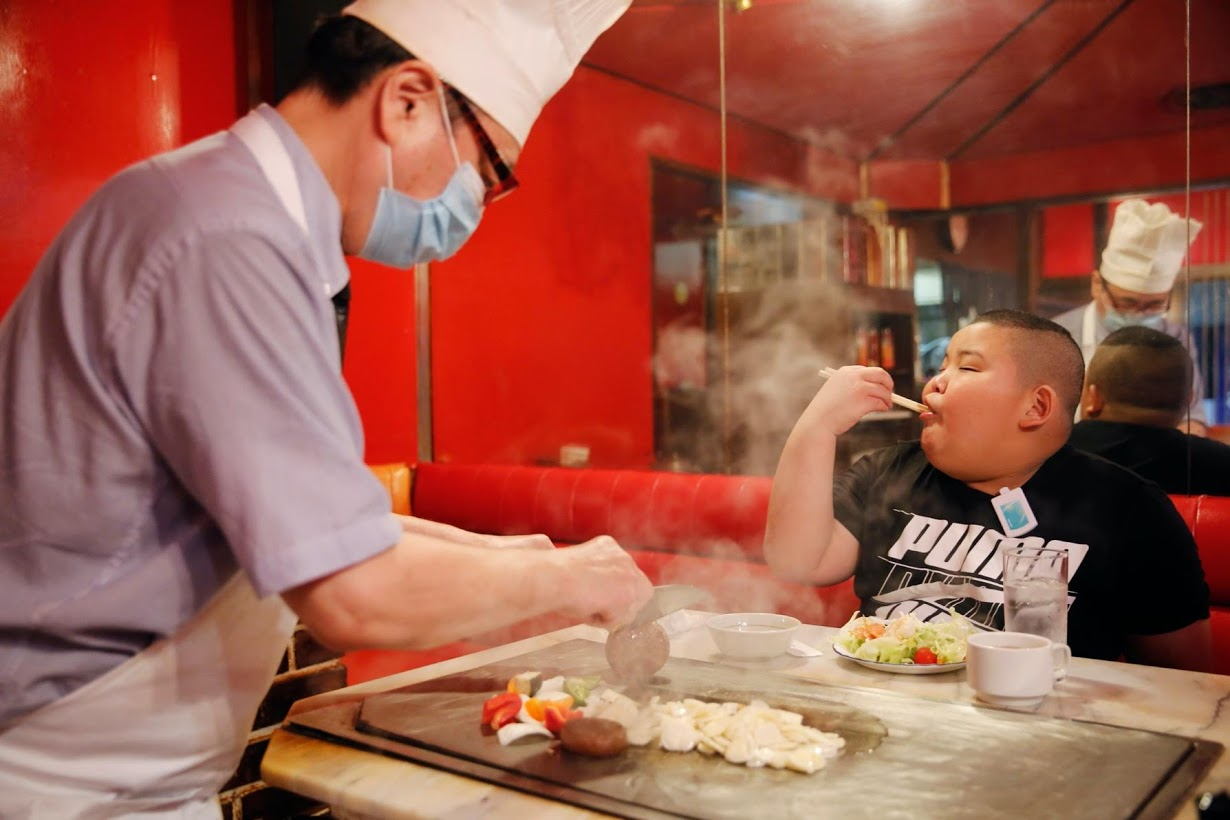 Kyuta eats steak, which his father bought him as a reward after training, at 'Chime', a restaurant in Tokyo. Photo: Reuters