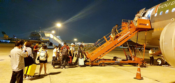 Passengers of Jetstar Pacific, currently Pacific Airlines, board the airplane at night. Photo: C.Trung / Tuoi Tre