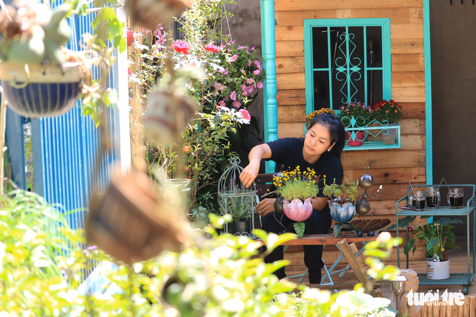 Nhu Ngoc cares for potted plants in her mini garden. Photo: Nhat Thinh / Tuoi Tre