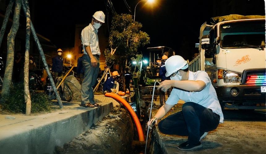 Technicians check a cable trench's depth. Photo: V.A / Tuoi Tre