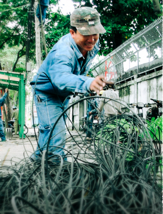 A worker cleans up old wires after being removed on Truong Dinh Street on May 12, 2009. Photo: Nguyen Cong Thanh / Tuoi Tre