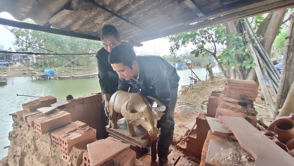Nguyen Van Hoang brings a large-sized clay buffalo to the firing process at Thanh Ha Pottery Village in Hoi An City, Quang Nam Province, Vietnam. Photo: D.T. / Tuoi Tre