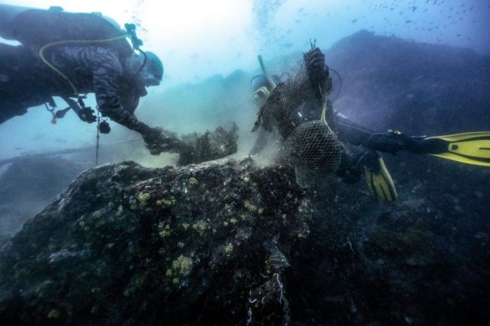Divers untangle a fishing net caught around a reef off the coast of Thailand. Photo: AFP