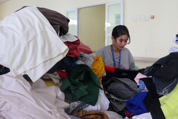 A female student inspects donated clothes before packaging and distribution. Photo: Nhat Thu / Tuoi Tre