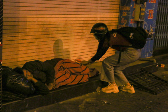A female volunteer from Anh Den Dem offers support to a homeless man. Photo: Huu Huong / Tuoi Tre