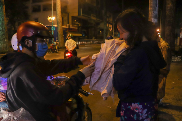 A homeless woman is happily accepts a donated coat from Anh Den Dem. Photo: Nhat Thu / Tuoi Tre