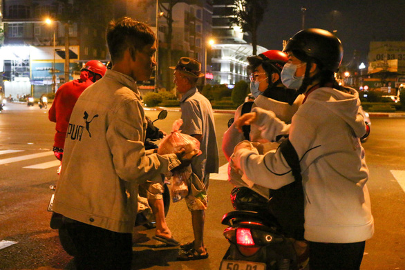 Two female volunteers from Anh Den Dem offer a donation to a man in Ho Chi Minh City. Photo: Huu Huong / Tuoi Tre