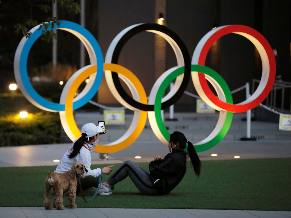 Women work out in front of the Olympic rings near the National Stadium in Tokyo, Japan January 22, 2021. Photo: Reuters
