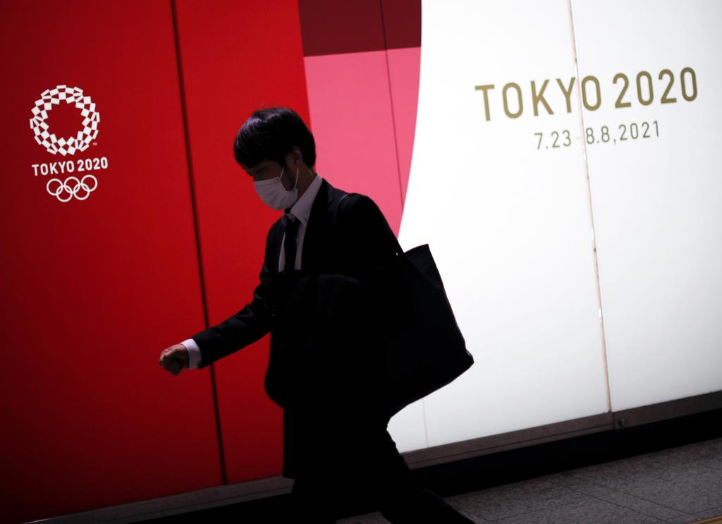 A man wearing a protective face mask walks past an advertising of Tokyo 2020 Olympic Games that have been postponed to 2021 due to the coronavirus disease (COVID-19) outbreak, in Tokyo, Japan January 22, 2021. Photo: Reuters