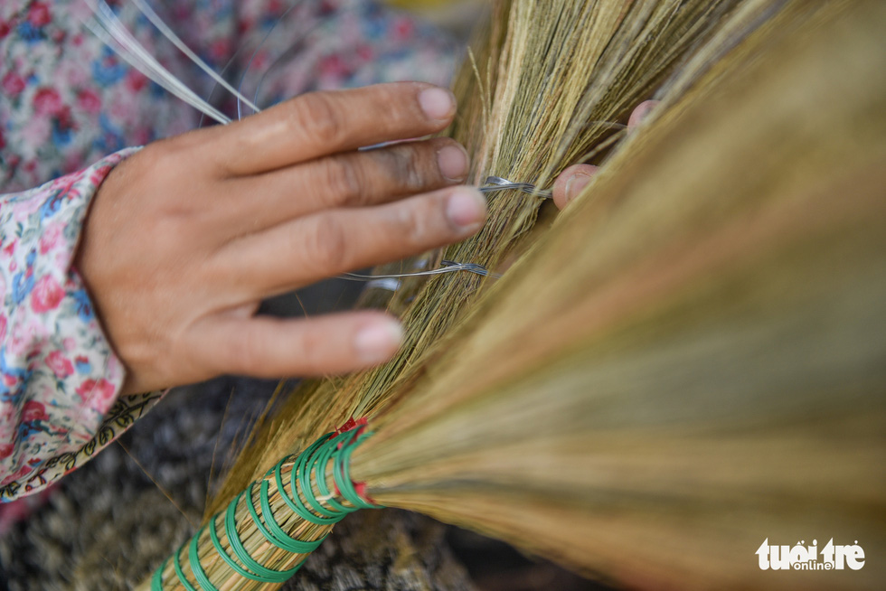 A worker braids a broom with a metal thread, another stage of making a broomstick. Photo: Minh Phuong / Tuoi Tre