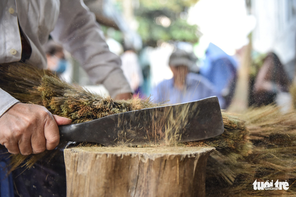 Chopping the stick to make a perfect broom is another step when making a broom. Photo: Minh Phuong / Tuoi Tre