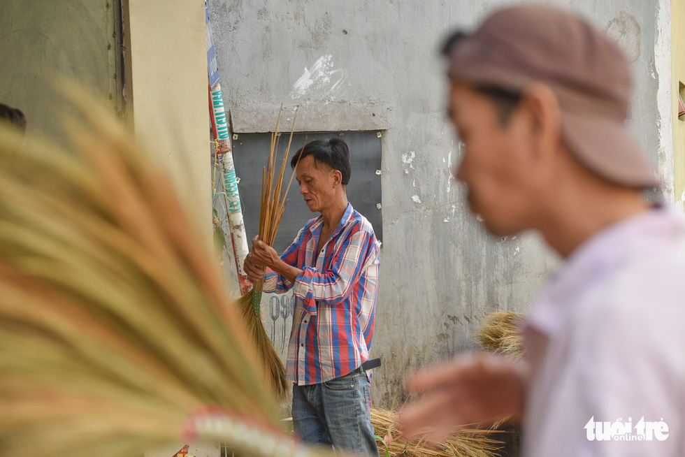 Nguyen Huu Hieu, 48, bundles a broom in a way he has done for the last 20 years. Photo: Minh Phuong / Tuoi Tre