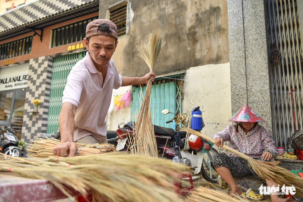 "Nguyen Thanh Quang, 47, who has 30 years of experience making brooms, bundles ""Dot"" sticks to make a broom. Photo: Minh Phuong / Tuoi Tre"