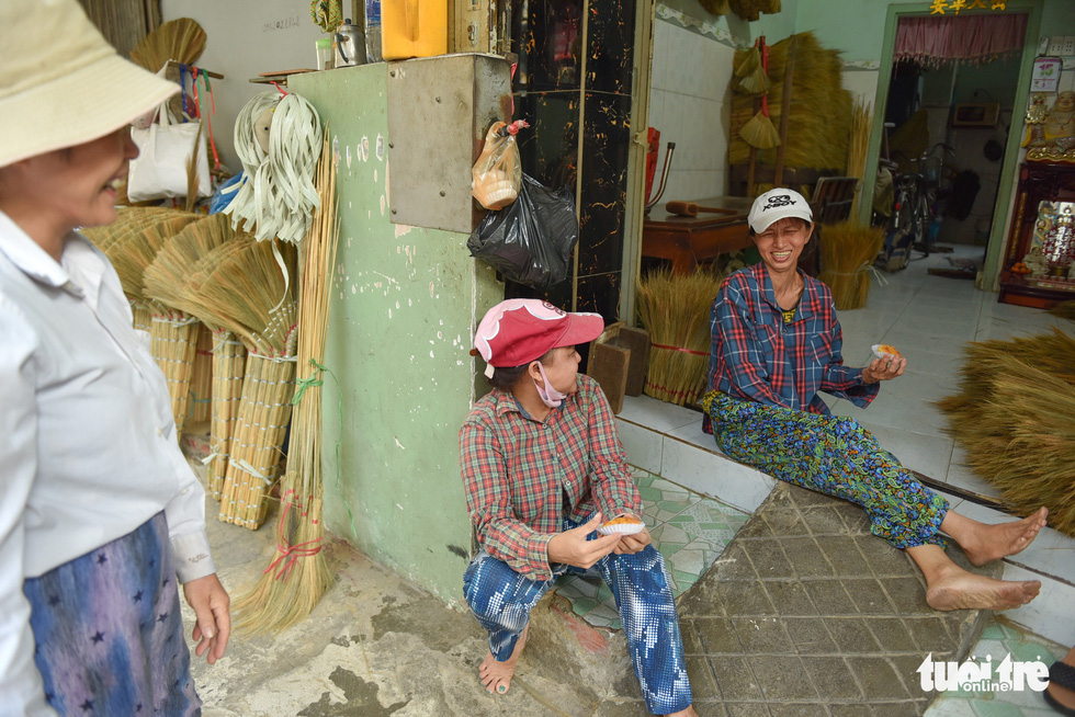 Three workers laugh with each other during a short break after working hours. Photo: Minh Phuong / Tuoi Tre