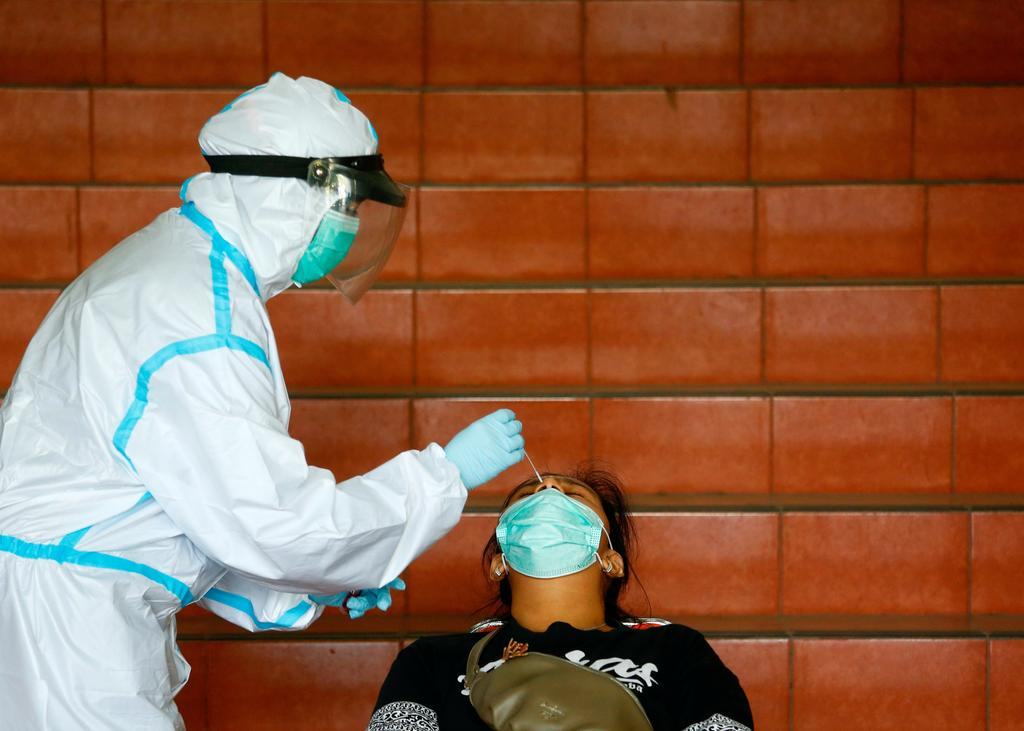 A medical worker wearing personal protective equipment (PPE) collects a swab sample from a woman to be tested for the coronavirus disease (COVID-19) as the outbreak continues, at the Patriot Chandrabhaga stadium in Bekasi, Indonesia, January 26, 2021. Photo: Reuters