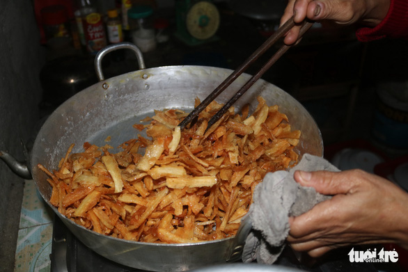 Le Thi Tu sugarcoats pieces of candied cassava in her kitchen in Thua Thien – Hue Province. Photo: Nguyen Trong / Tuoi Tre