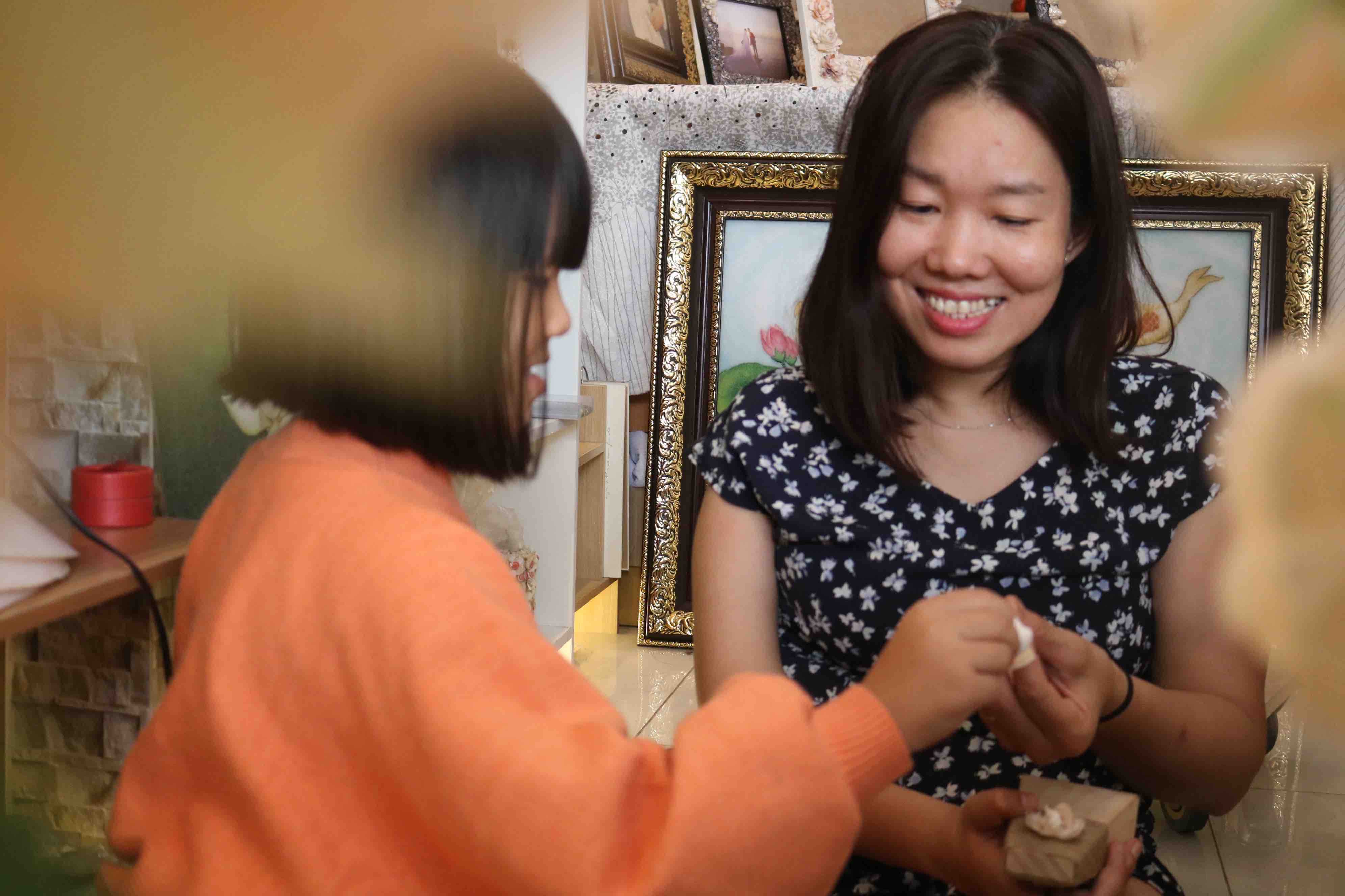 Artist Tran Thi Ngoc Hieu instructs her daughter the shell painting technique at her shop at District 1, Ho Chi Minh City. Photo: Hoang An / Tuoi Tre