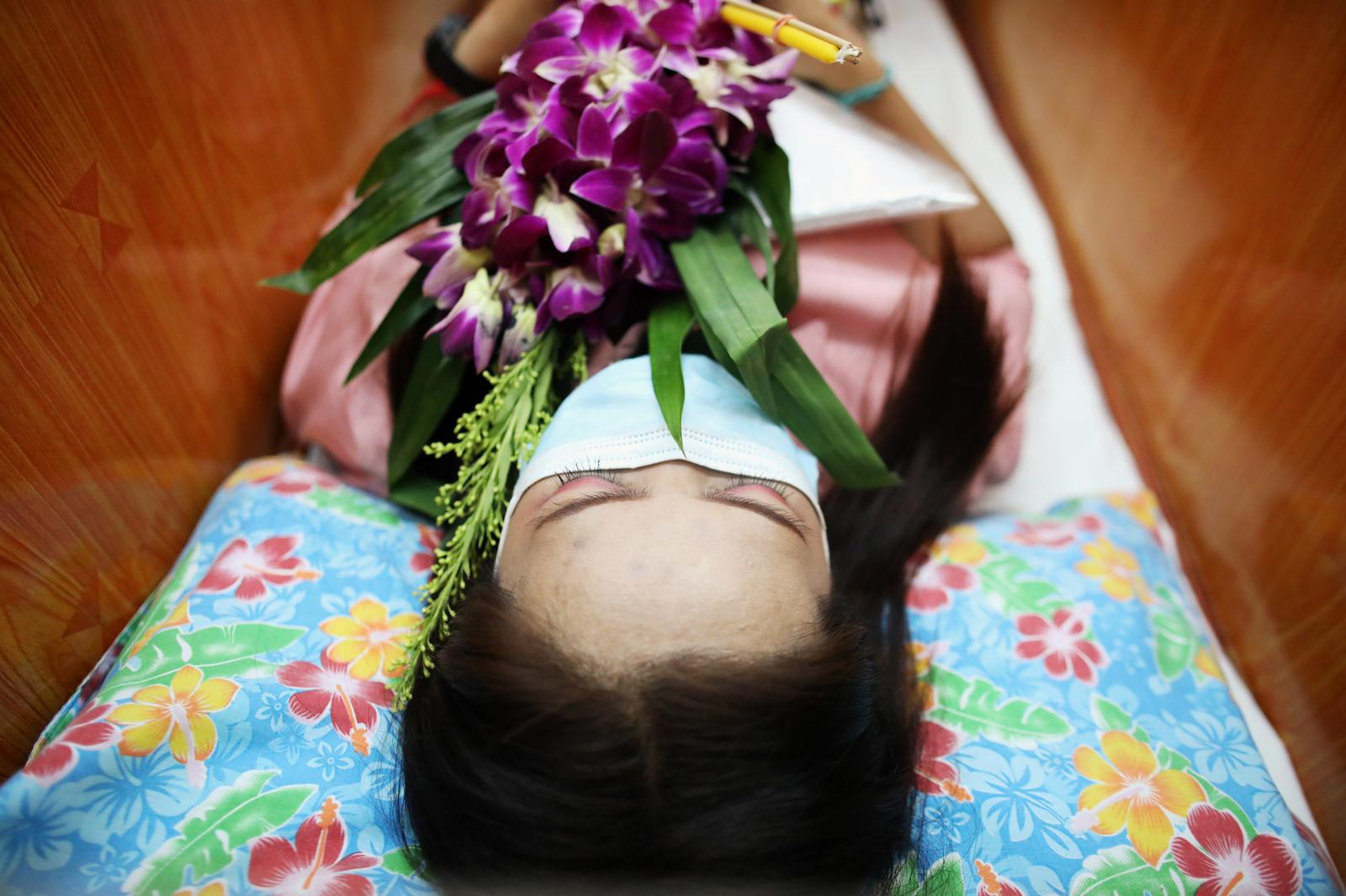 A devotee lies down and prays inside a coffin to trick death and improve luck at a temple in Bangkok, Thailand January 27, 2021. Photo: Reuters