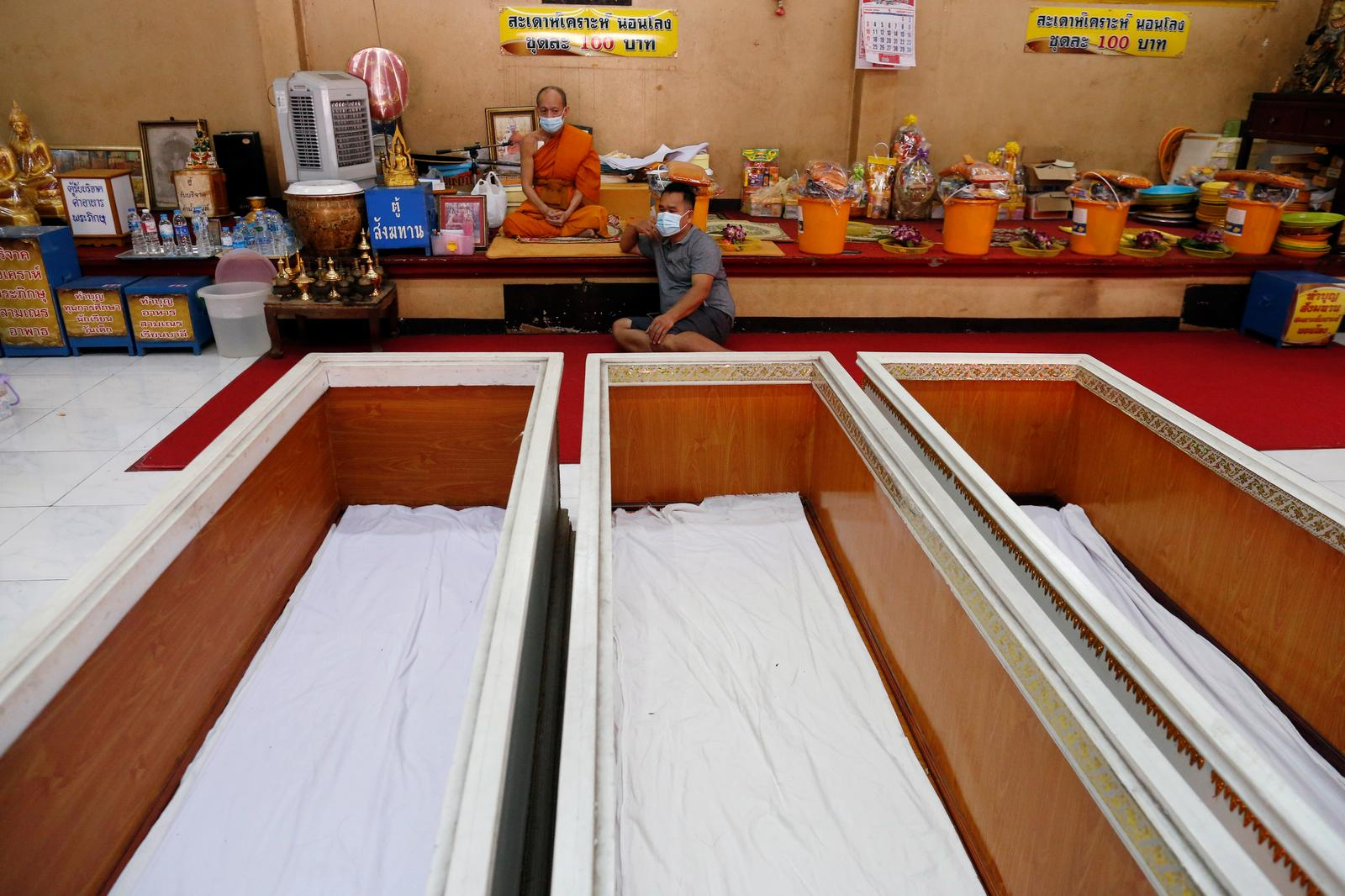 Coffins are seen for devotees to lie down in to pray in a ritual to trick death and change their luck at a temple in Bangkok, Thailand January 27, 2021. Photo: Reuters