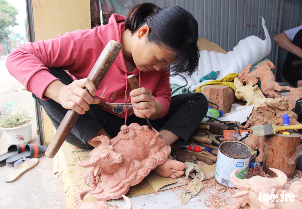 Tran Thi Thuong carves a wooden buffalo at Dinh Quan Village, Tien Phong Commune of Thuong Tin District, Hanoi. Photo: Ha Quan / Tuoi Tre