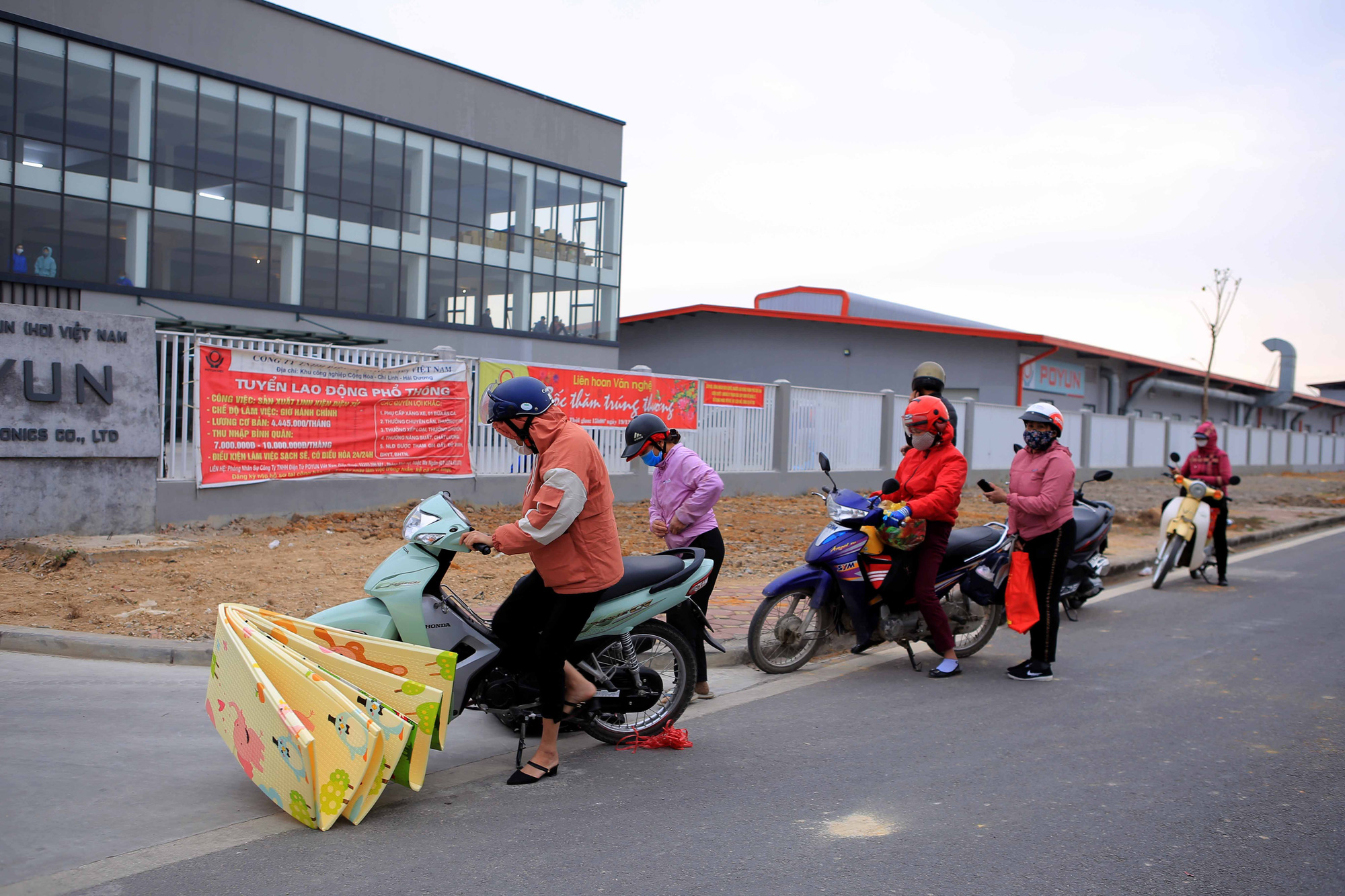 Family members give supplies to workers at Vietnam Poyun Electronics in Hai Duong Province, Vietnam, January 28, 2021. Photo: Anh Cuong / Tuoi Tre