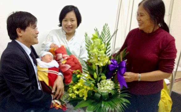 Dr. Le Luong Van Ve and his wife visited Hoang Thi Kim Dung (center) after she gave birth to her twin boys from her dead husband's frozen sperm in 2013. Dr. Ve, who successfully performed the miracle procedure, and his wife also act as the newborns' godparents. Photo: Tuoi Tre