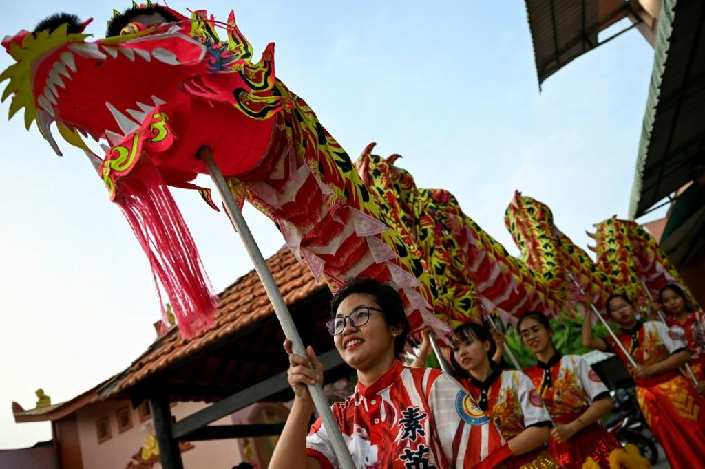 Le Yen Quyen (left) had to overcome local resistance to women joining the Tu Anh Duong lion and dragon dance troupe in Can Tho, Vietnam. Photo: AFP