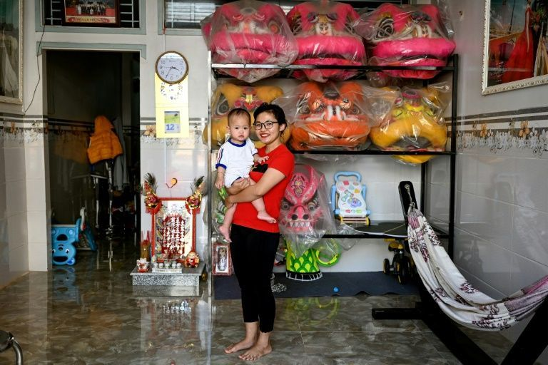 'I am proud to be the person who has inspired other girls,' says lion dancer Le Yen Quyen whose baby daughter accompanies her to practices. Photo: AFP