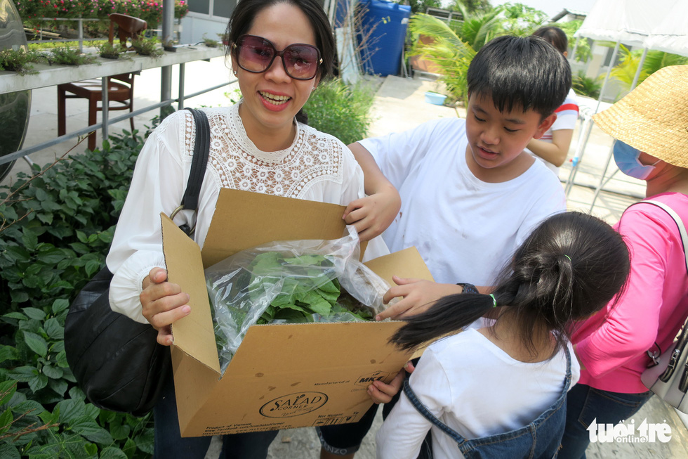 Huong and her children carry fresh produce harvested from at Mekong Farm in Ho Chi Minh City. Photo: T.T.D. / Tuoi Tre