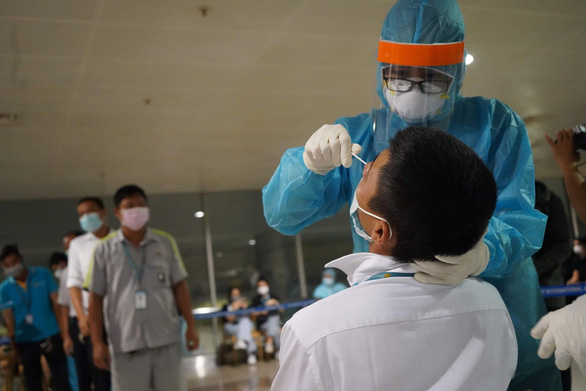 Medical staff is taking sample for COVID-19 test on an employee at Tan Son Nhat Airport in Ho Chi Minh City as a request to test 1,000 airport employees from the city's Department of Health on February 6, 2021. Photo: T.H/ Tuoi Tre