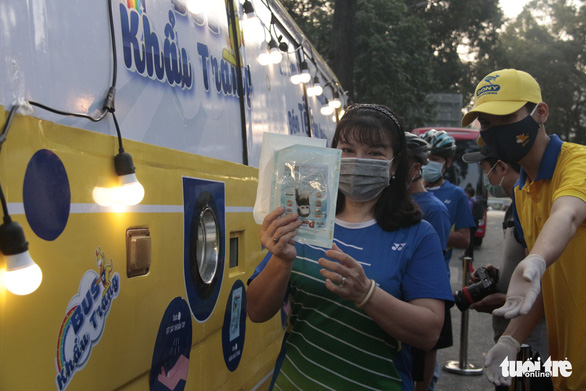 A woman shows free masks she received from a bus at the Ho Chi Minh City Youth Culture House in District 1 on February 6, 2021. Photo: Cong Trieu/ Tuoi Tre