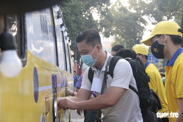 A man gets his hands sanitized before getting face masks for free from a bus at the Ho Chi Minh City Youth Culture House in District 1 on February 6, 2021. Photo: Cong Trieu/ Tuoi Tre