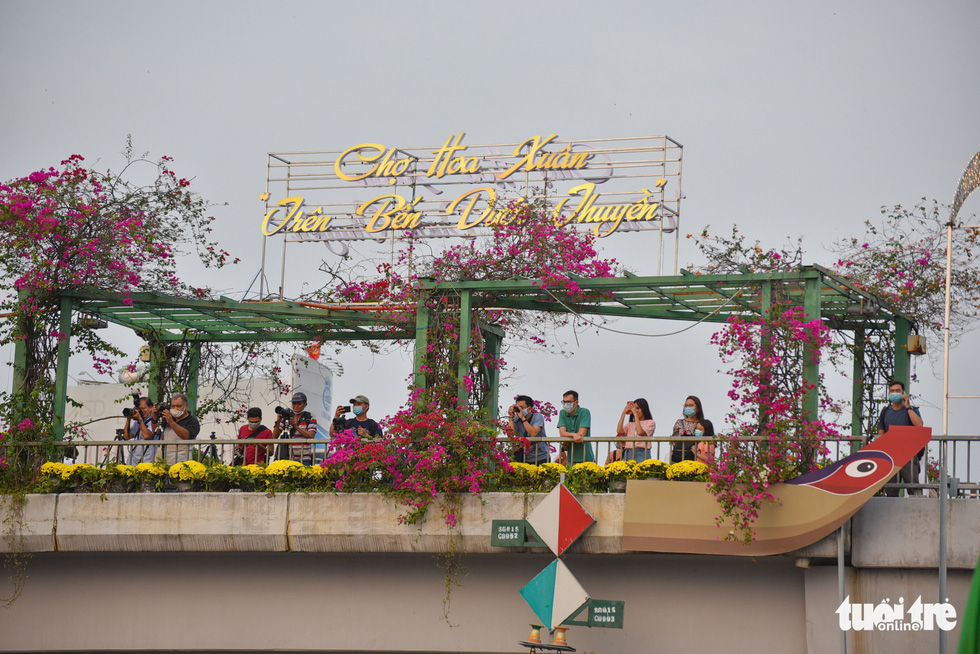 Visitors standing on a bridge for a view down to the spring flower festival at Binh Dong Wharf along Tau Hu Canal in Ho Chi Minh City's District 8 on February 6, 2021. Photo: Ngoc Phuong/ Tuoi Tre