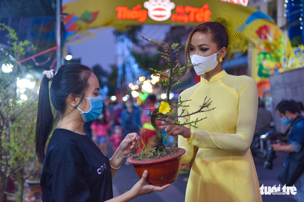 Miss Universe Vietnam 2017 H'Hen Nie (right) donning ao dai (Vietnamese traditional costume) while visiting the the spring flower festival at Binh Dong Wharf along Tau Hu Canal in Ho Chi Minh City's District 8 on February 6, 2021. Photo: Ngoc Phuong/ Tuoi Tre
