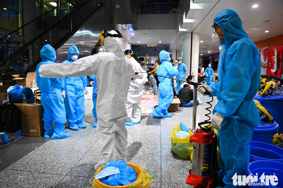 A medical worker is disinfected before taking sample for COVID-19 testing from Noi Bai International Airport (NIA) staffers, February 9, 2020. Photo: Hoang Phong / Tuoi Tre