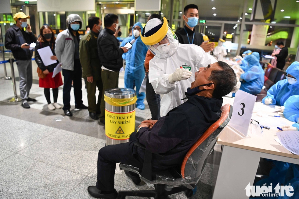 A medical worker collects sample for COVID-19 testing from a Noi Bai International Airport (NIA) staffer, February 9, 2020. Photo: Hoang Phong / Tuoi Tre