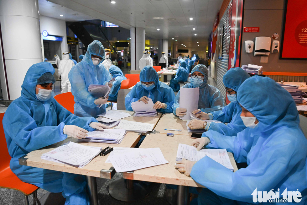 Medical workers process health declarations from Noi Bai International Airport (NIA) staffers, February 9, 2020. Photo: Hoang Phong / Tuoi Tre