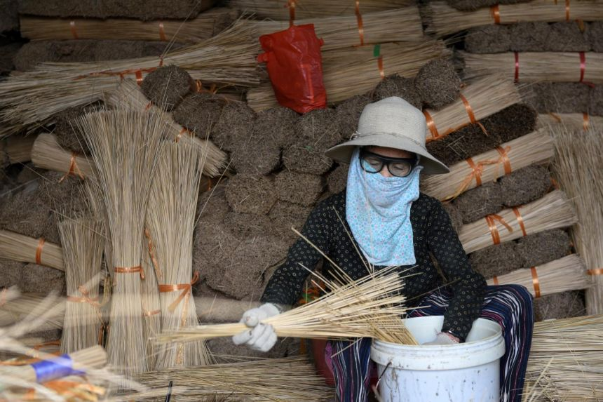 A woman prepares sticks for incense-dying. Photo: Reuters