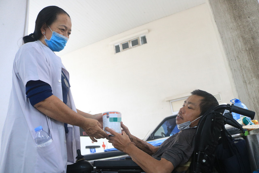 A woman gifts a can of milk powder to Nguyen Ngoc Em at Cho Ray Hospital in District 5, Ho Chi Minh City. Photo: Hoang Loc / Tuoi Tre