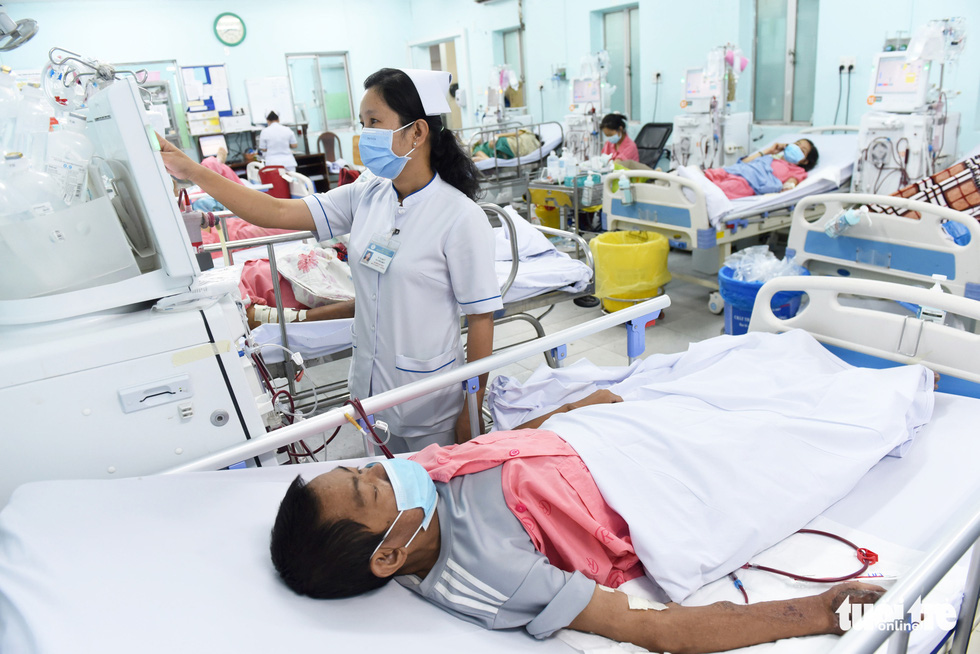 A nurse tends to Nguyen Ngoc Em at his bed in Cho Ray Hospital in District 5, Ho Chi Minh City. Photo: Duyen Phan / Tuoi Tre