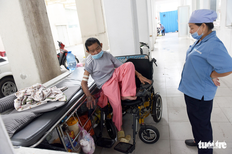 A staff member talks to Nguyen Ngoc Em at Cho Ray Hospital in District 5, Ho Chi Minh City. Photo: Duyen Phan / Tuoi Tre