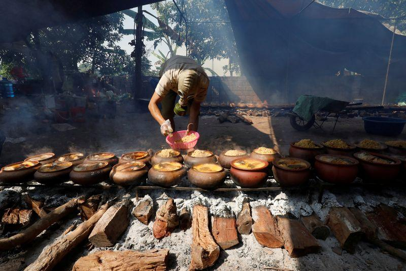 Tran Duc Phong wears a gas mask to braise black carp in claypots with longan firewood to serve as a traditional Vietnamese dish for Lunar New Year celebrations in Ha Nam province, Vietnam February 5, 2021. Photo: Reuters