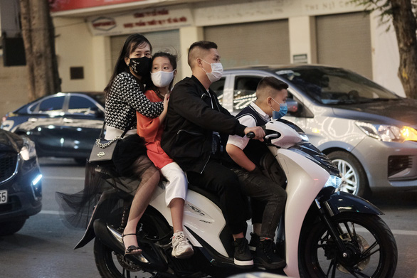 A motorbike carrying three people is seen in downtown Hanoi on February 12, 2021. Photo: Mai Thuong / Tuoi Tre