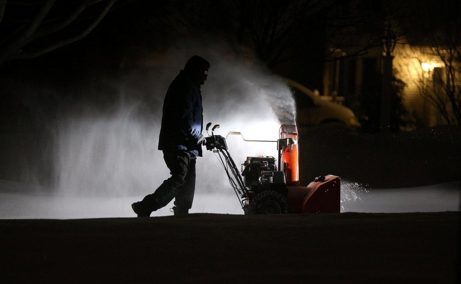 Roger Hake gets an assist from his truck lights as he clears snow from his driveway before the sun comes up in Webster, near Rochester, New York, U.S. February 16, 2021. Photo: Jamie Germano/Rochester Democrat and Chronicle/USA Today Network via REUTERS