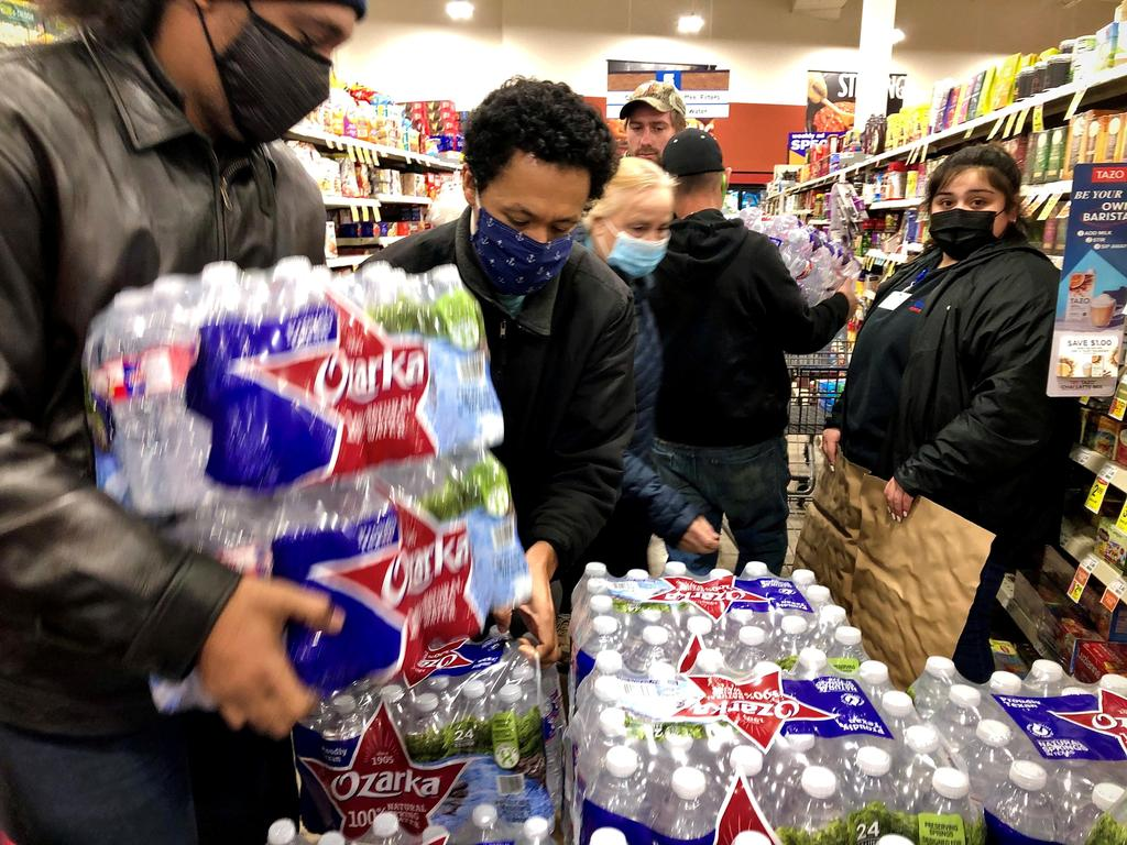 Shoppers crowd a display of bottled water at a United Supermarkets location not long after the city announced it had 2-3 hours of water left at normal consumption, due to loss of electric power caused by the winter storm in Abilene, Texas, U.S. February 15, 2021. Picture taken February 15, 2021. Photo: Ronald W. Erdrich/Reporter-News/USA Today Network via REUTERS. NO RESALES. NO ARCHIVES. MANDATORY CREDIT